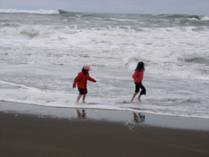 Two young children playing in waves on beach on a cloudy, chilly day