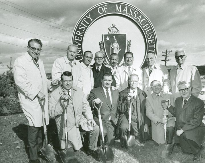 old ground breaking photo, 13 men holding shovels, large University of Massachusetts Medical School logo/structure behind them