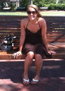 Woman sitting on bench in park on a summer day smiling for the camera