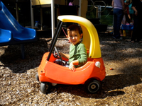 little boy in toddler plastic play car