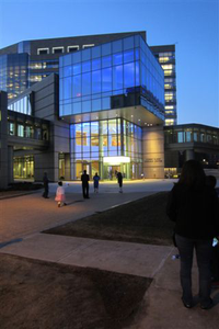 photo of Albert Sherman Center entrance, highlighting the entrance which is all lit up against an evening sky