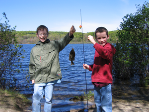 Two boys by a lake holding up the fish they caught and their fishing pole, smiling for the camera