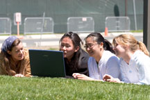 students on lawn with laptop