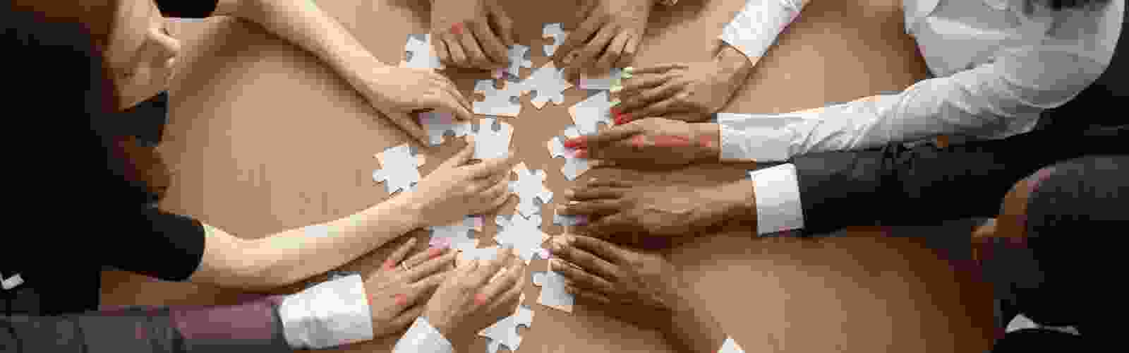 hands of people gathered around a table with jigsaw puzzle pieces