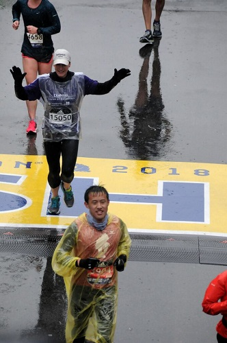 Laura Alonso, MD, crossing the Boston Marathon finish line