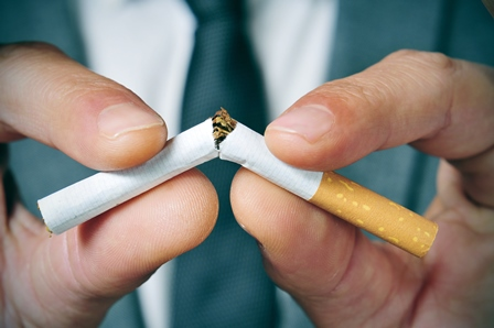 a man in a business suit breaking a cigarette in half