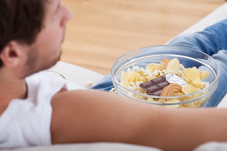 man on couch with a big bowl full of snacks