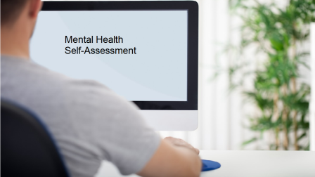 man in front of computer screen looking at mental health self assessment