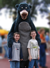 Two kids smiling and posing with Blu from Disney's Jungle Book, and